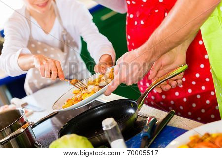 Family cooking meal in domestic kitchen and boy  is trying a bit