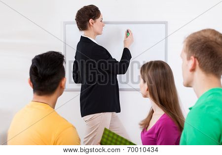 Teacher Writing On Whiteboard At Classroom