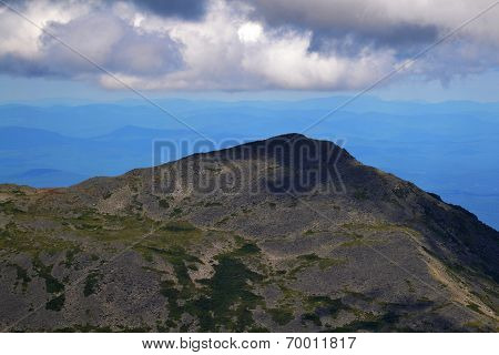 Clouds Sitting Over A High Mountain Top