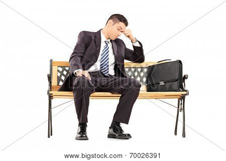 Tired businessman sitting on a bench isolated on white background