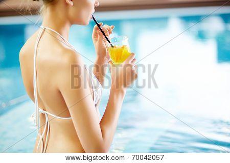 Girl drinking lemonade in swimming pool