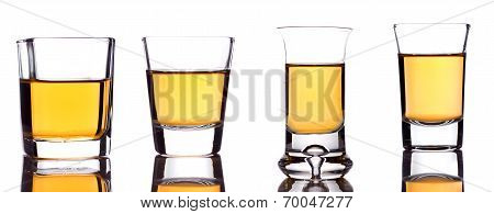 A Closeup Of A Group Of Shot-glasses Partially Full Of An Alcoholic Drink On White