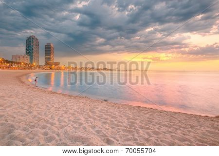 Barceloneta Beach in Barcelona with colorful sky at sunrise poster
