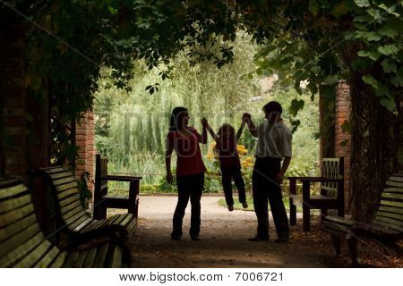 Parents and little girl in summer garden in plant tunnel. Girl plays being shaken on hands of parent