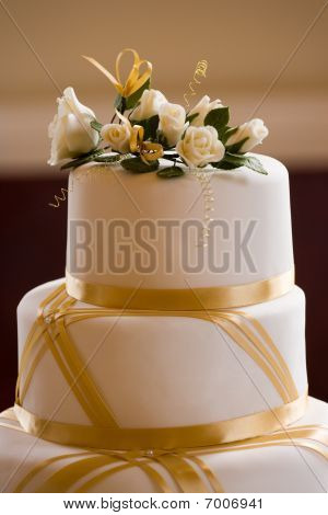 Top Of Wedding Cake Decorated With Roses And Gold Ribbon