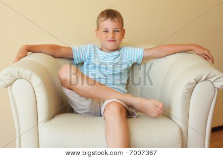 Boy Freely Sitting With Magnificent Easy Chair In Cosy Room