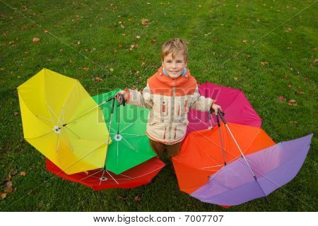 Boy in autumn park in environment of multi-coloured umbrellas. Top view.