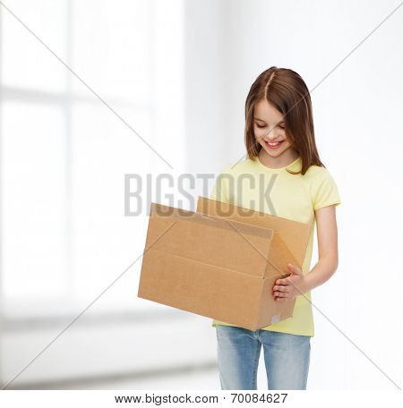 advertising, childhood, delivery, mail and people - smiling girl holding open cardboard box and looking into it over white room background