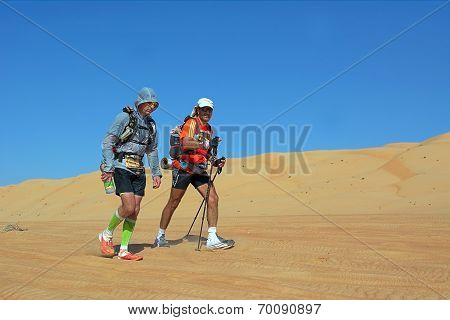 Two Unidentified Runners Running In Desert