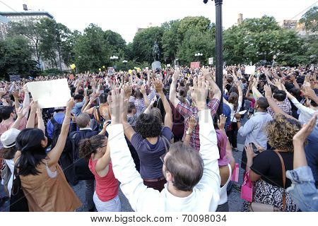 Demonstrators raise their arms to chant,
