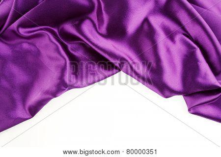 Closeup of purple silk fabric on plain background