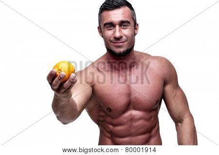 Happy muscular man holding orange over white background