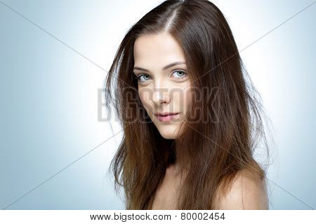 Closeup portrait of a young cute girl over blue background