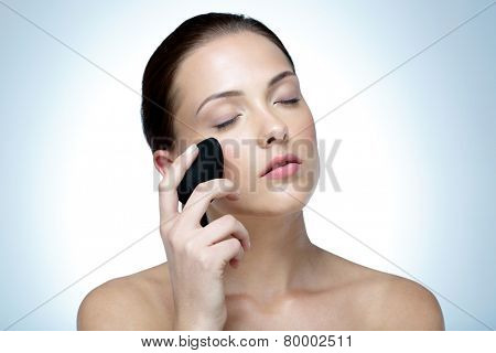 Woman applying foundation by sponge on face for make-up with closed eyes