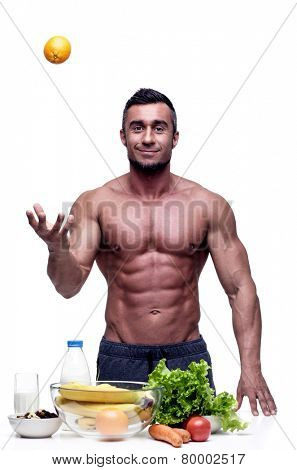 Cheerful muscular man standing with healthy food