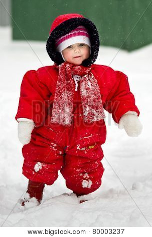 Cute Little Baby Clothing In Big Jumpers In The Snowy Park