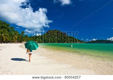 Woman with umbrella at beautiful beach at Seychelles