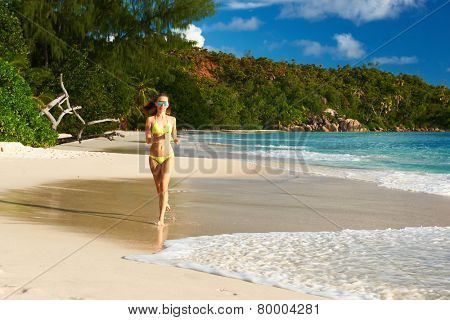 Woman in bikini running at tropical beach at Seychelles