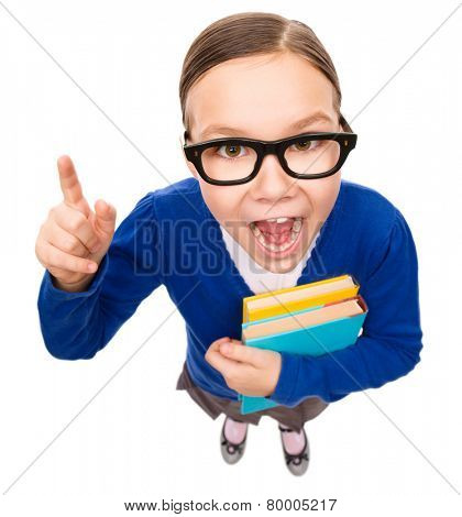 Funny little girl is holding books and explaining something pointing with her index finger, fisheye portrait, isolated over white