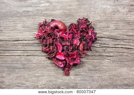 Heart From Red Dry Petals On Wooden Table