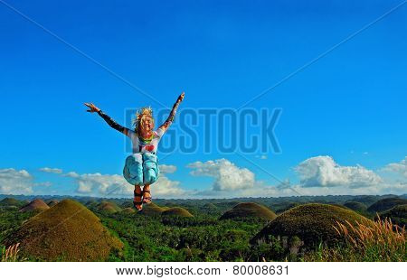 Young woman jumping on the chocolate hill