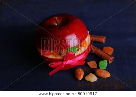 Red apple stuffed with dried fruits with cinnamon and almond on color wooden background