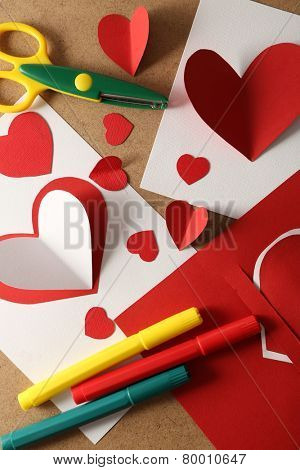 Beautiful hand made post cards, pens and scissors  with paper hearts on color wooden background