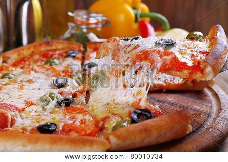 Pizza with cheese on board and wooden table background
