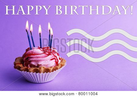 Cake with birthday candles on purple background