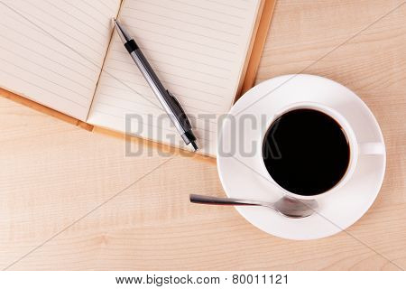 Cup of coffee on saucer with open notebook and pen on wooden table background