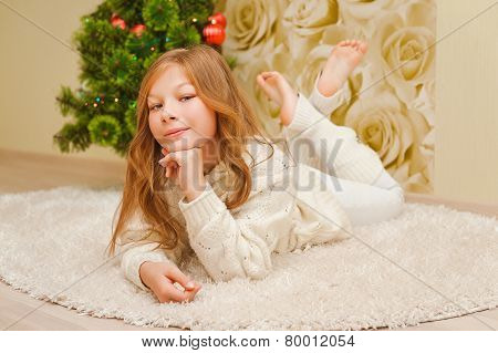 Child laying down near Christmas tree