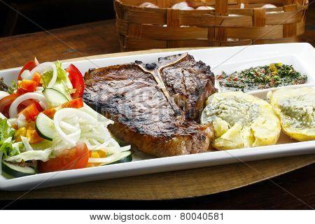 t bone steak with potato salad and vegetables