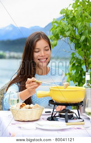 Cheese fondue - woman eating local Swiss food. People eating traditional food from Switzerland having fun by lake in the Alps on travel in Europe.