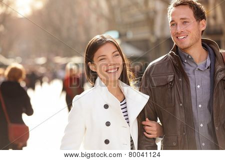 Urban modern young professionals couple walking romantic laughing talking holding hands on date. Young multicultural couple Asian and Caucasian on La Rambla Barcelona, Catalonia, Spain.