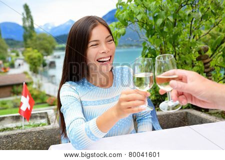 People having fun drinking white wine at dinner laughing. Romantic couple sitting at table in Swiss Alps by lake in Switzerland. Romantic couple toasting enjoying wine.