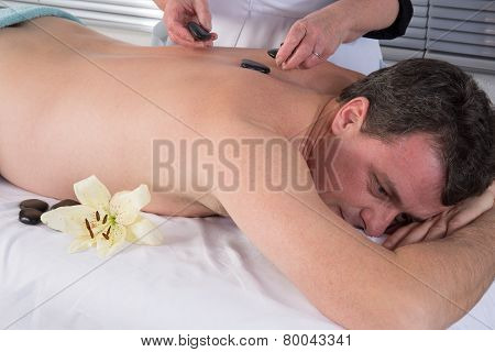 Image Of Hand Placing Lastone On Man's Back In Spa