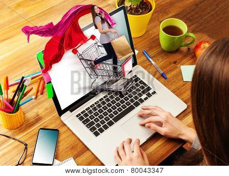 Woman working with laptop placed on wooden desk. Shot from aerial view