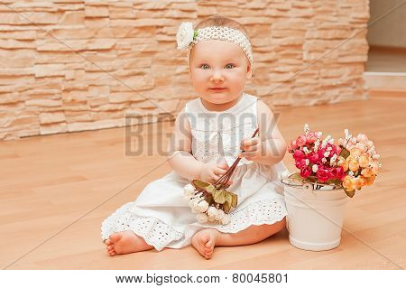 Cute girl in dress sitting on the floor among the flowers
