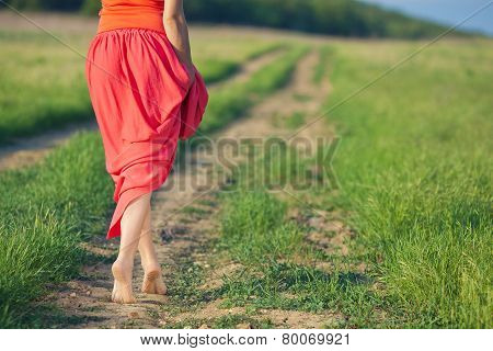 Portrait of barefoot woman in long red dress walking on the road in the green field in summer