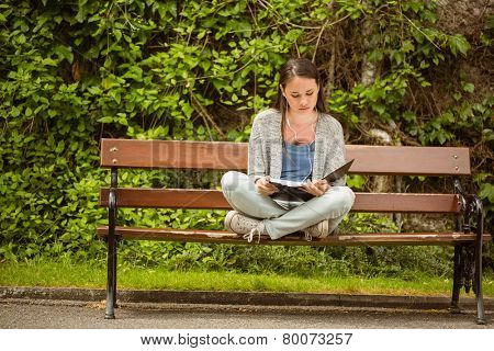 Student sitting on bench listening music with mobile phone and revising in park at school