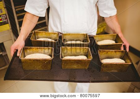 Baker holding tray of loaf tins in a commercial kitchen