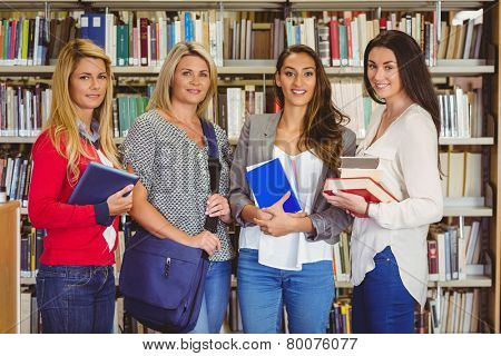 Smiling students standing beside shelf smiling at camera in library