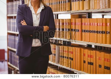 Mature female librarian posing with crossed arms in library