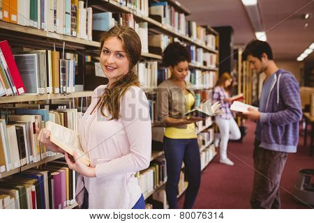 Happy student taking book from shelf in library