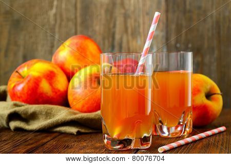 Glass of apple juice with apples on wood background