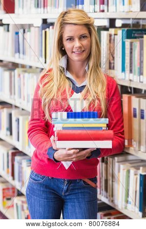 Mature student in library holding books at the university