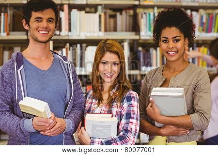 Students standing and smiling at camera holding books in library