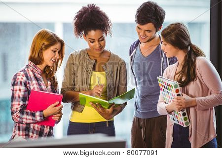 Students standing and chatting together in library