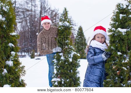 Happy father and kid in Santa hats with christmas tree outdoor