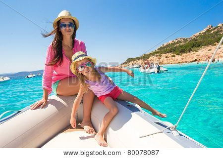 Young mother with adorable daughter enjoy vacation on boat